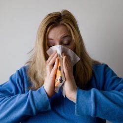 Sick woman, blowing her nose