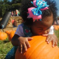 girl with mouth on pumpkin